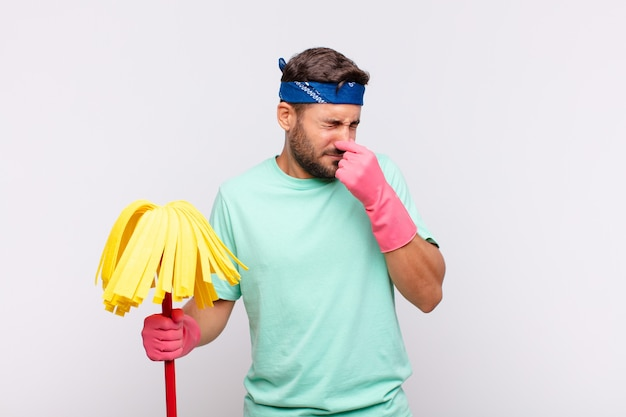 Jeune homme se sentant dégoûté, tenant le nez pour éviter de sentir une odeur nauséabonde et désagréable