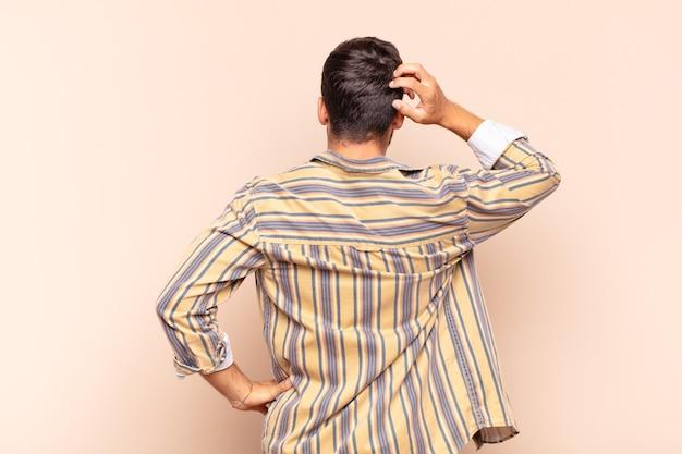 Jeune homme se sentant désemparé et confus, pensant à une solution, avec la main sur la hanche et d'autres sur la tête, vue arrière
