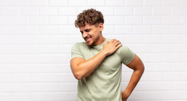 Jeune homme se sentant fatigué, stressé, anxieux, frustré et déprimé, souffrant de douleurs au dos ou au cou