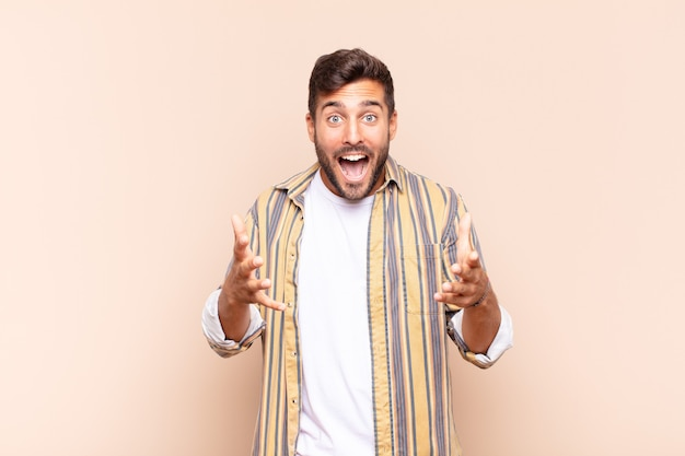 Un jeune homme se sentant heureux, étonné, chanceux et surpris, comme dire omg sérieusement? incroyable