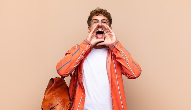 Jeune homme se sentant heureux, excité et positif, donnant un grand cri avec les mains à côté de la bouche, appelant. concept étudiant