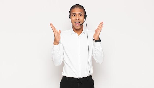 Jeune homme se sentant heureux, excité, surpris ou choqué, souriant et étonné de quelque chose d'incroyable