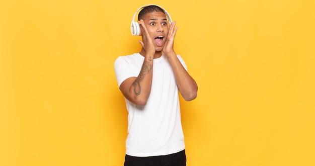 Jeune homme se sentant heureux, excité et surpris, regardant sur le côté avec les deux mains sur le visage