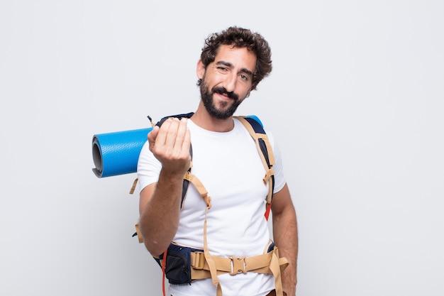 Jeune homme se sentant heureux, prospère et confiant, faisant face à un défi et disant: amenez-le! ou vous accueillir