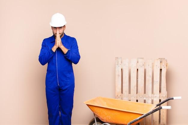 Jeune homme se sentant inquiet, plein d'espoir et religieux, priant fidèlement avec les paumes pressées, implorant le concept de construction de pardon