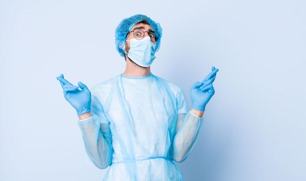 Jeune homme se sentant nerveux et plein d'espoir, croisant les doigts, priant et espérant bonne chance. concept de coronavirus
