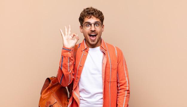 Jeune homme se sentant réussi et satisfait, souriant avec la bouche grande ouverte, faisant signe correct avec la main