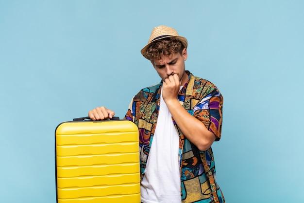 Jeune homme se sentant sérieux, attentionné et concerné, regardant de côté avec la main pressée contre le menton. concept de vacances