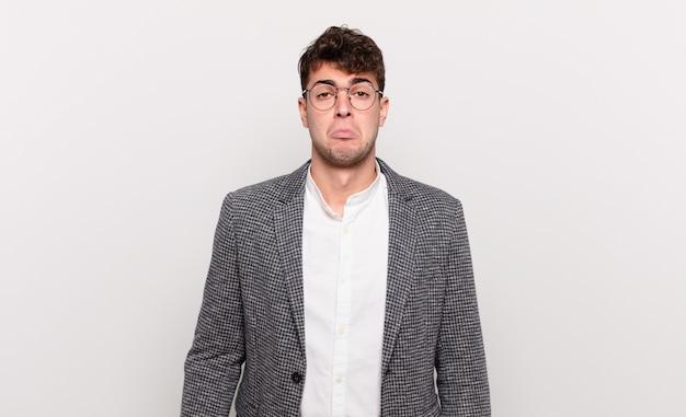 Jeune homme se sentant triste et pleurnichard avec un regard malheureux, pleurant avec une attitude négative et frustrée