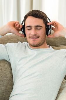 Jeune homme se sentir détendu tout en écoutant de la musique avec des écouteurs dans le salon