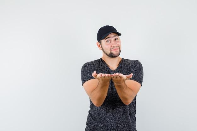 Jeune homme se tenant la main comme présenter quelque chose en vue de face de t-shirt et casquette.