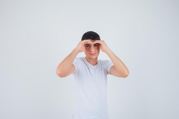 Jeune homme se tenant la main pour voir clairement en t-shirt et à la recherche concentré. vue de face.