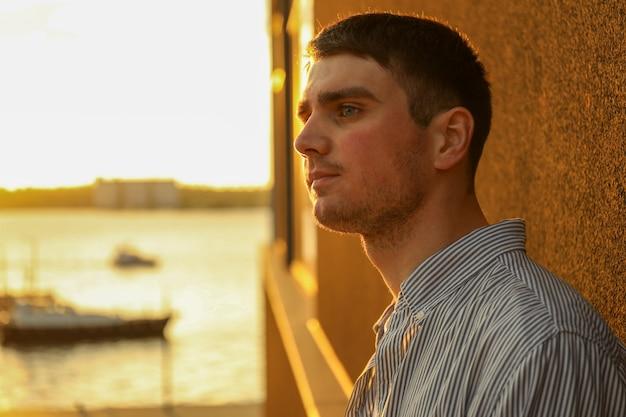 Jeune homme se tient appuyé contre un mur.