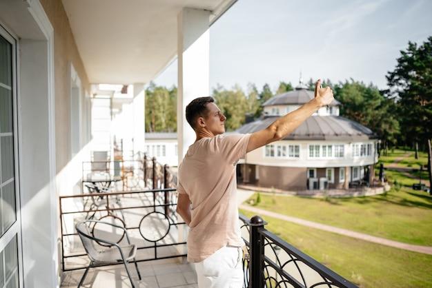 Un jeune homme se tient sur le balcon d'un hôtel et prend des selfies sur son téléphone portable