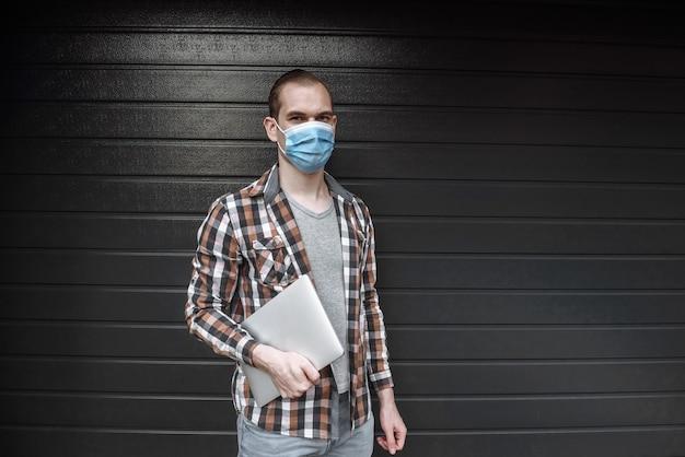 Un jeune homme se tient contre un mur dans un masque médical de protection avec un ordinateur portable
