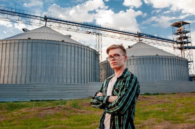 Un jeune homme se tient près d'un entrepôt de céréales