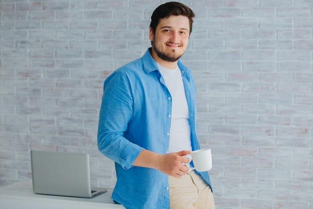 Un jeune homme se tient à la table avec un ordinateur portable et une tasse de café