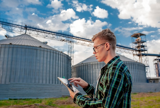Un jeune homme se tient avec une tablette près d'un ascenseur métallique dans une zone agricole. un entrepôt de céréales.