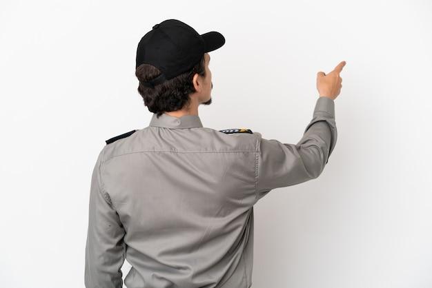 Jeune homme de sécurité caucasien isolé sur fond blanc pointant vers l'arrière avec l'index