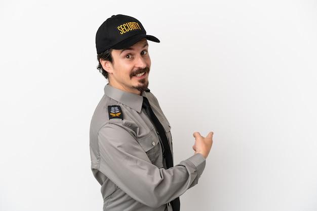 Jeune homme de sécurité caucasien isolé sur fond blanc pointant vers l'arrière