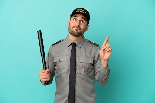 Jeune homme de sécurité isolé sur fond bleu avec les doigts croisés et souhaitant le meilleur