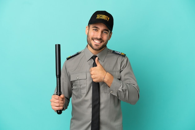 Jeune homme de sécurité isolé sur fond bleu donnant un coup de pouce geste