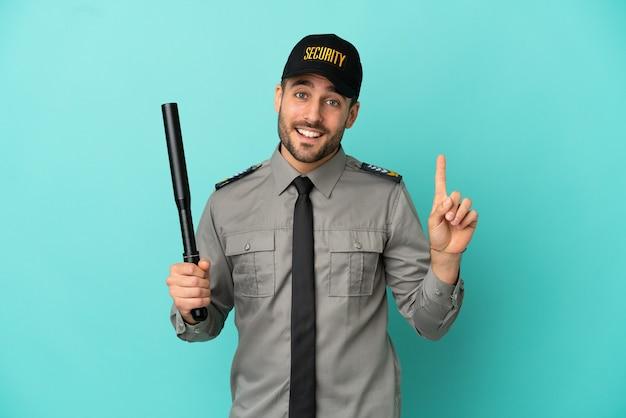 Jeune homme de sécurité isolé sur fond bleu montrant et levant un doigt en signe du meilleur