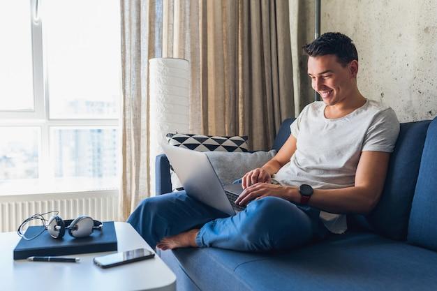 Jeune homme séduisant assis sur un canapé à la maison travaillant sur un ordinateur portable en ligne, à l'aide d'internet