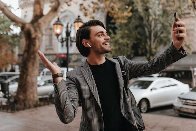 Jeune homme séduisant aux cheveux bruns en t-shirt noir et blazer gris, tenant un téléphone, portant des écouteurs, souriant et montrant la ville par chat vidéo
