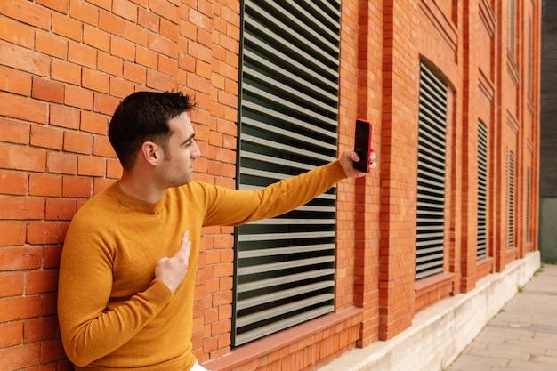 Jeune homme séduisant aux traits hispaniques, prenant un selfie ou une photo en vêtements jaunes appuyé sur un mur. concept de mode de vie et de voyage.