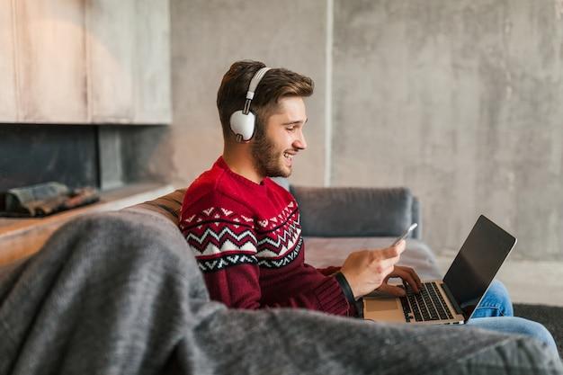 Jeune homme séduisant sur le canapé à la maison en hiver avec smartphone dans les écouteurs, écouter de la musique, porter un pull en tricot rouge, travaillant sur ordinateur portable, pigiste