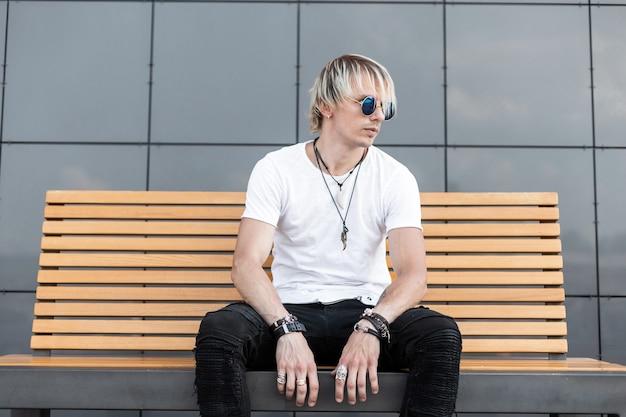 Jeune homme séduisant avec une coiffure à la mode dans des lunettes de soleil à la mode dans un élégant t-shirt en jeans est assis sur un banc en bois dans la ville. beau mec blond se détend à l'extérieur. style d'été.