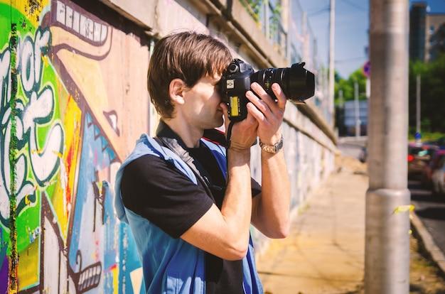 Jeune homme séduisant dans un t-shirt noir et un gilet bleu prend des photos dans une rue de la ville