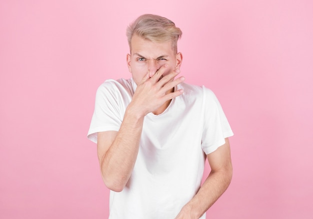 Jeune homme séduisant avec dégoût sur son visage se pince le nez, quelque chose pue, sur fond rose. expression faciale des émotions négatives.