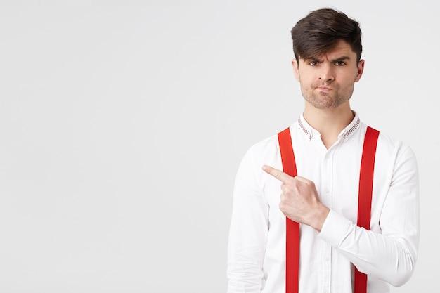 Jeune homme séduisant élégant en chemise blanche et porte-jarretelles rouge pointant avec l'index vers le côté gauche avec une expression faciale mécontente et mécontente