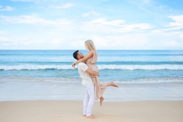 Jeune homme séduisant et femme amoureuse à pied et câlin sur le sable blanc et la mer azur. voyage, lune de miel