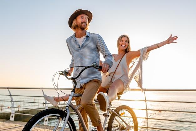 Jeune homme séduisant et femme voyageant à vélo, couple romantique en vacances d'été au bord de la mer au coucher du soleil, tenue de style boho hipster, amis s'amusant ensemble