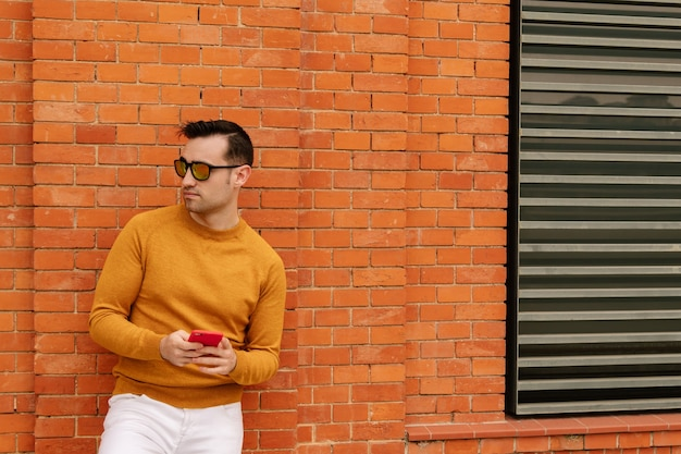 Jeune homme séduisant en lunettes de soleil orange utilisant son smartphone, vêtu de vêtements jaunes et de murs de briques. concept de mode de vie.