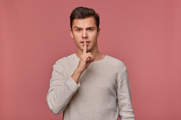Jeune homme séduisant en manches longues vierges, se tient sur fond rose et montre un geste de silence, veuillez rester calme et silencieux .;