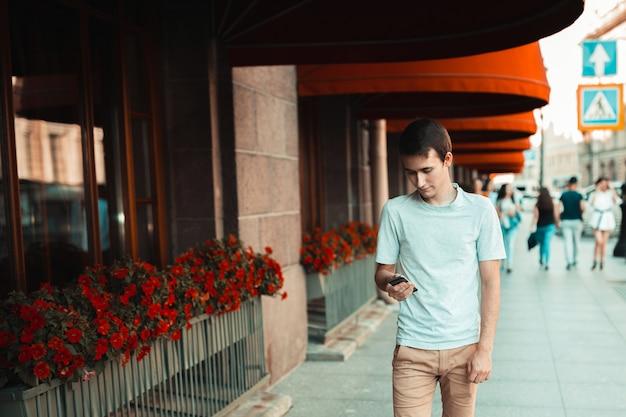 Jeune homme séduisant, marchant dans la ville et à l'aide de smartphone