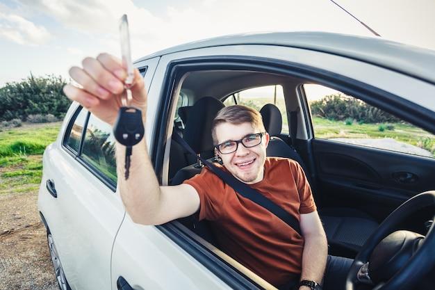 Jeune homme séduisant montrant ses nouvelles clés de voiture et souriant.