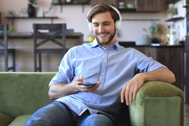 Jeune homme séduisant se reposant sur un canapé à la maison et utilisant un téléphone portable pour vérifier ses e-mails.