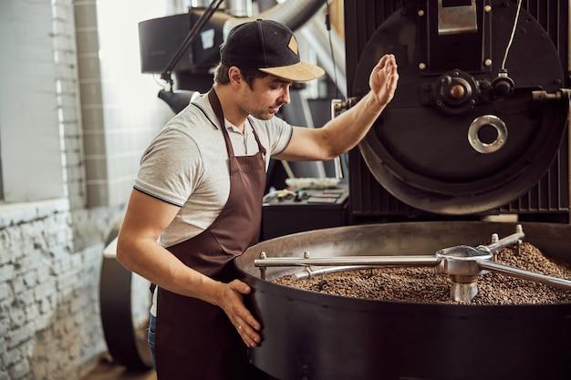 Jeune homme séduisant en tablier vérifiant les grains de café torréfiés dans un plateau de refroidissement tout en utilisant la machine à torréfier le café
