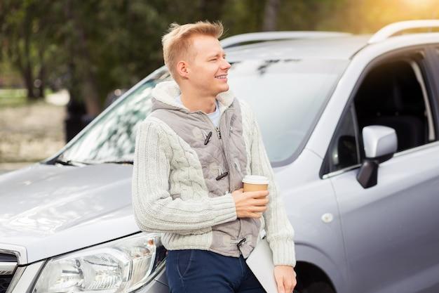 Jeune homme séduisant avec une tasse de café en papier dans la voiture