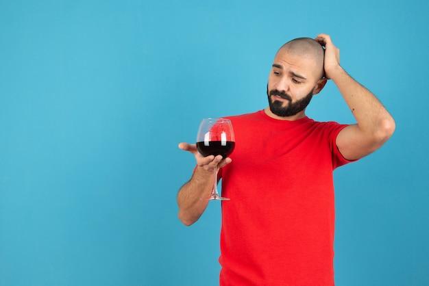 Jeune homme séduisant tenant un verre de vin rouge contre le mur bleu.