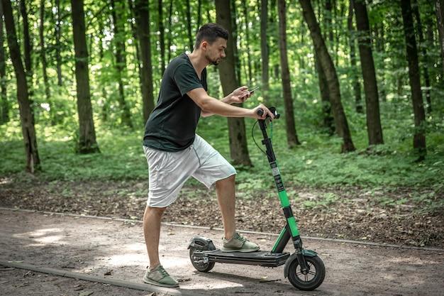 Jeune homme séduisant utilisant son smartphone en se tenant dans la rue avec un scooter électrique.