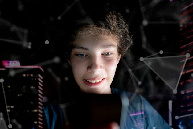 Jeune homme séduisant utilise son téléphone portable tard dans la nuit dans une pièce sombre