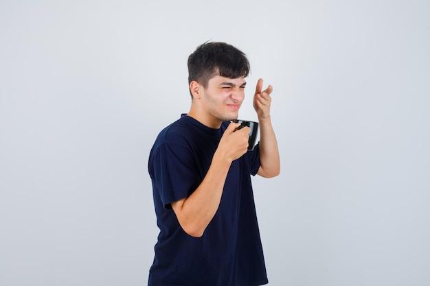 Jeune homme sentant le café en tasse en t-shirt noir et à la dégoûté. vue de face.