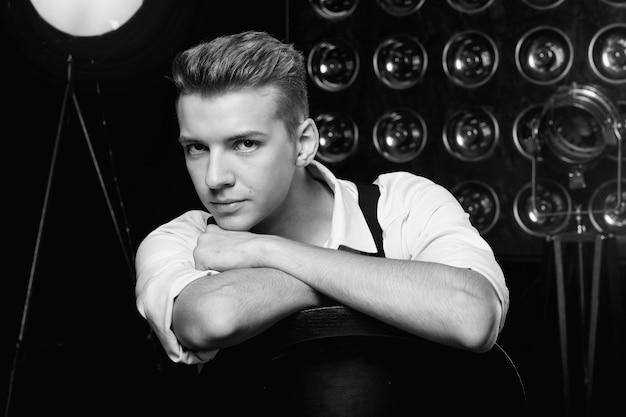 Jeune homme sérieux sur chaise, portrait en gros plan, mannequin, photo en noir et blanc
