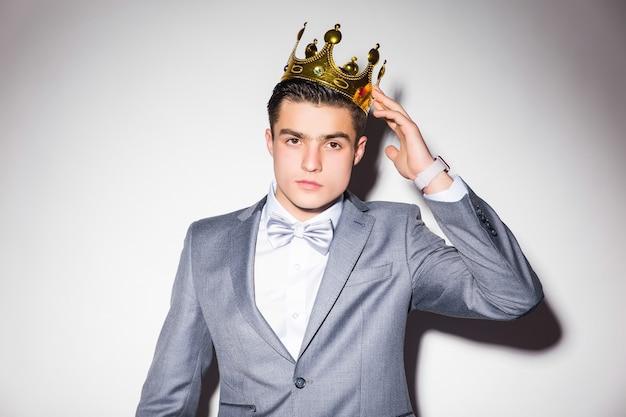 Jeune homme sérieux en costume-cravate, tenant une couronne d'or sur sa tête, sur un mur blanc